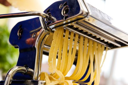 fettuccine: Fettuccine coming out of a manual pastamachine - shallow depth of field with focus on the pasta