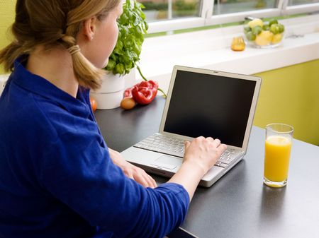 A female using the computer in the Kitchen Stock Photo - 1756433