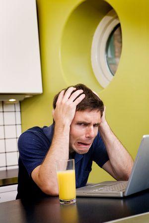 彼の顔に絶望的な表情で彼の台所に座っている、心配しているコンピューターのユーザー 写真素材