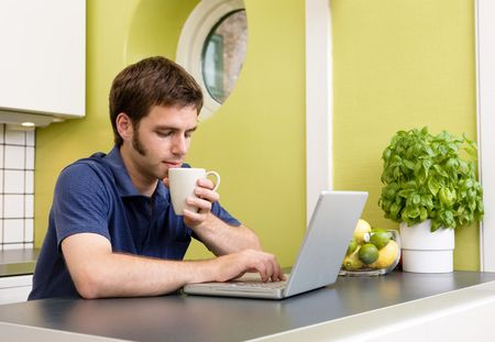 warm drink: A young man uses the computer in the kitchen while enjoying a warm drink. Stock Photo