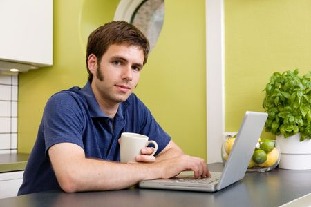 warm drink: A young man uses the computer in the kitchen while enjoying a warm drink