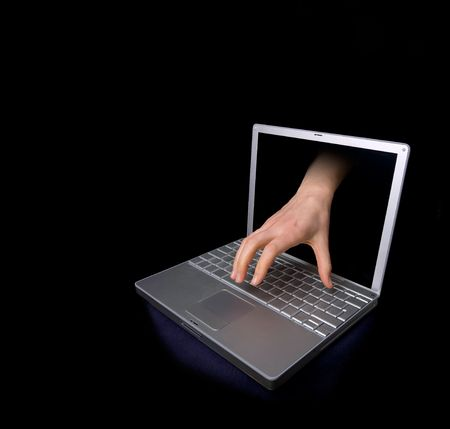 A hacker concept image of a hand coming through the computer. photo