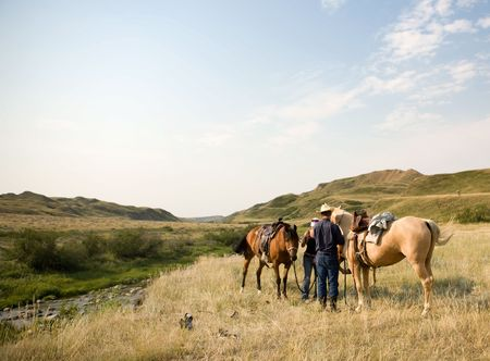 horse riding: A couple of people ready to go on a ride accross rolling prairie hills