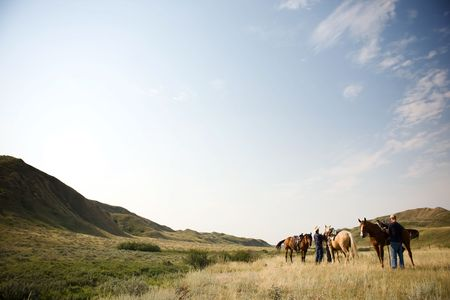 cowboy on horse: A couple of people ready to go on a ride accross rolling prairie hills