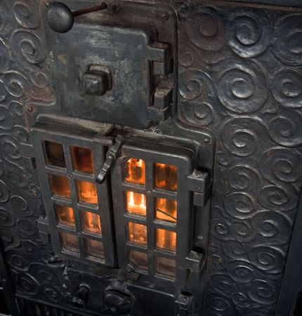 An old cast iron oven with flames viewable through the window photo