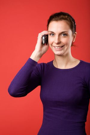 A casual portrait of a brunette caucasian female talking on a cell phone with a red background Stock Photo - 2346394