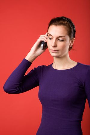 A casual portrait of a brunette caucasian female talking on a cell phone with a red background Stock Photo - 2346392