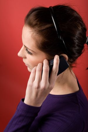 A young female listening on a cell phone. isolated on red. Stock Photo - 2346396