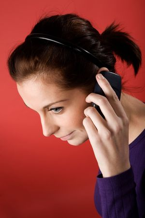 A young female listening on a cell phone. isolated on red. Stock Photo - 2346389