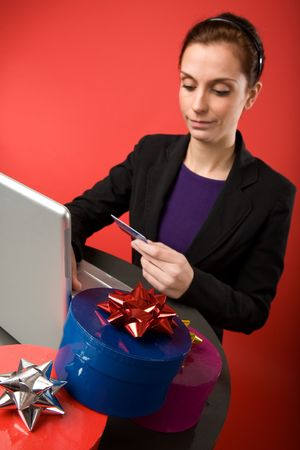 A young female shopping for christmas presents online.  Focus is on the presents with the model and computer blurred. photo