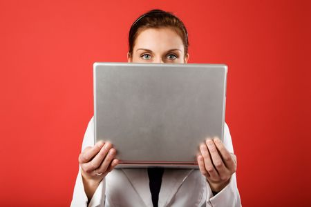 A young woman hiding behind and using a laptop computer wirelessly Stock Photo - 2346352