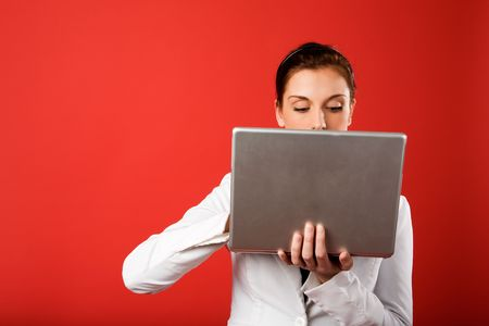 A young woman hiding behind and using a laptop computer wirelessly photo