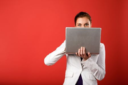 A young woman hiding behind and using a laptop computer wirelessly Stock Photo - 2346307