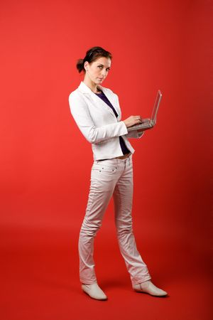 admire: A young woman typing on a laptop computer isolated on red