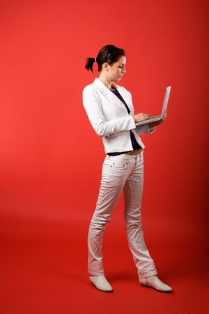 A young woman typing on a laptop computer isolated on red photo