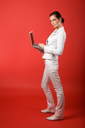 A young woman typing on a laptop computer isolated on red Stock Photo - 2346313