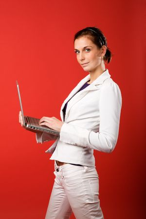 A young woman typing on a laptop computer isolated on red Stock Photo - 2346316