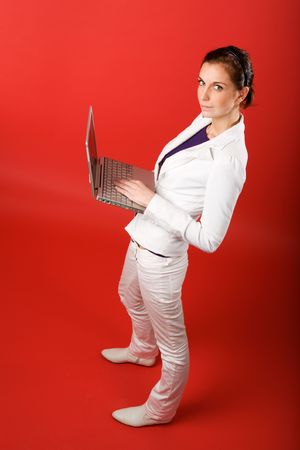 A young woman typing on a laptop computer isolated on red Stock Photo - 2346323