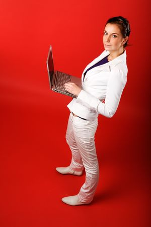 A young woman typing on a laptop computer isolated on red Stock Photo - 2346309