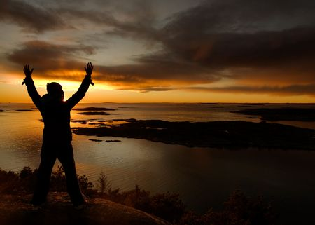 fredrikstad: A person standing by the ocean raising their arms in celebration