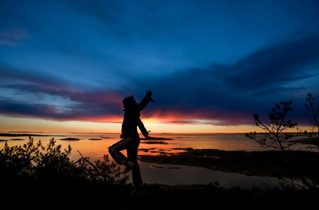 fredrikstad: A person running by the ocean raising their arms in celebration