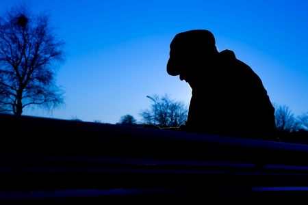 A depressed thoughtful sitting on a park bench in cold winter scene. Reklamní fotografie