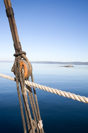 rigger: A boat pulley and rope system against a ocean landscape.