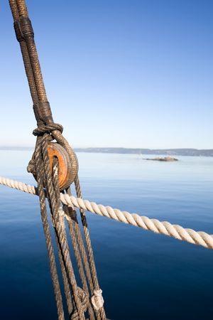 polea: Un barco de la polea y la cuerda en contra de un sistema de paisaje del oc�ano. Foto de archivo