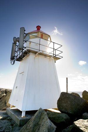 rocky point: Un piccolo faro su un promontorio roccioso punto contro il sole