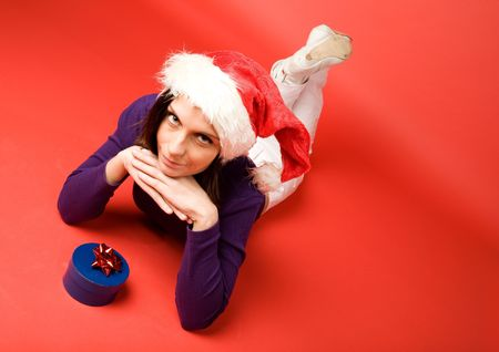 A young woman with a present isolated on red photo