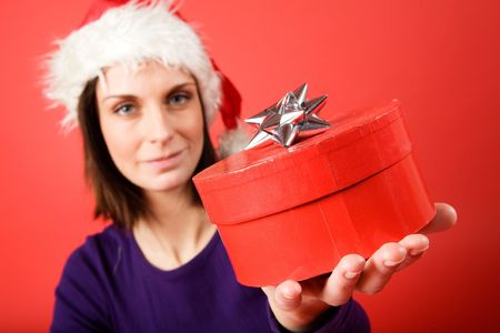 A young woman with a present isolated on red - shallow depth of field with the focus on the present box. photo