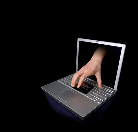 Credit card being stolen by a hand through the internet.  The credit card is fictitious. photo