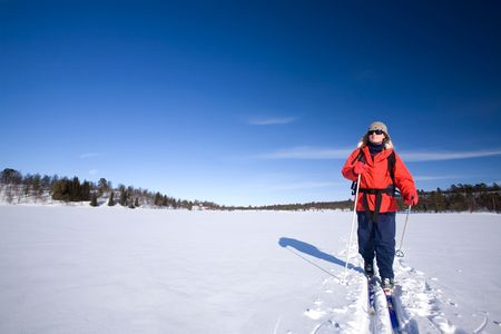 snow break: A woman cross country skiing across a frozen lake Stock Photo