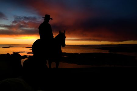 cowboy silhouette: A cowboy on a hill against a sunset and ocean