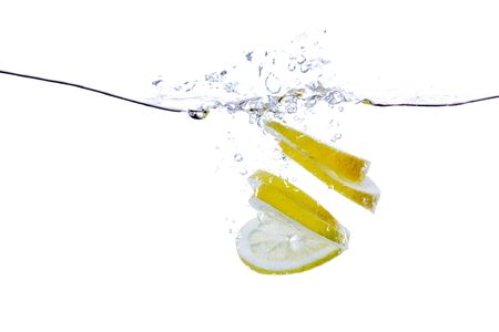 A group of lemon slices dropped in water with bubbles photo