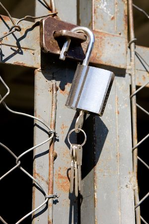 A heavy lock on a wire gate - open padlock with keys photo