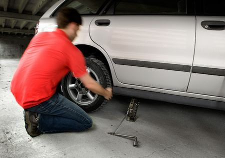quickly: A male changing a tire quickly