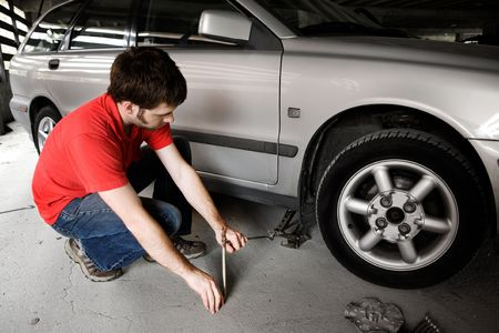 A male jacks up a car in a garage - fixing the wheel photo