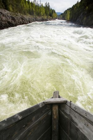 the rapids: An old wooden goat going down wild rapids