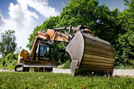 A backhoe sitting on grass photo