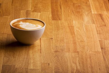 capucinno: A warm specialty coffe on a wood table Stock Photo