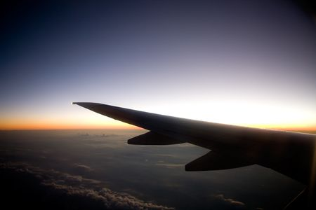 redeye: A wing on an airplane in flight at sunset Stock Photo