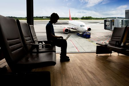 A young man using a laptop in an airport terminal Stock Photo - 3418702