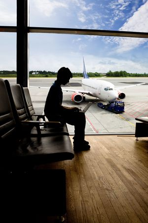 A young man using a laptop in an airport terminal photo