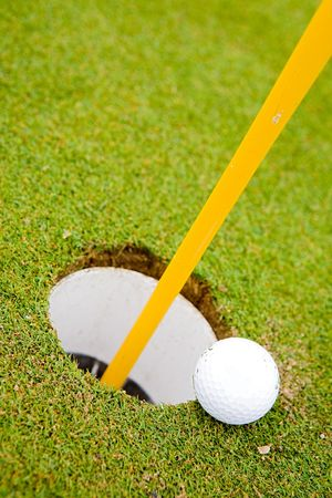 going in: Pelota de golf muy cerca de entrar en el agujero  Foto de archivo
