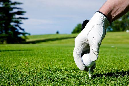A golfer sets up a tee at a driving range photo