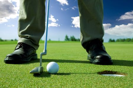 A golf put into the hole Stock Photo