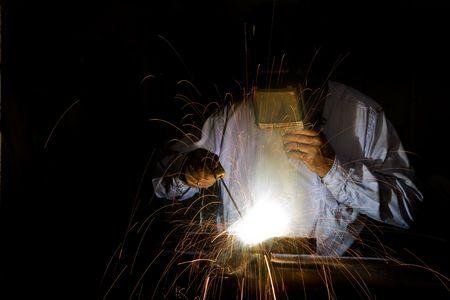 A male welding metal photo