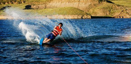 skieer: Een mannelijke waterskiën op een meer in de avond