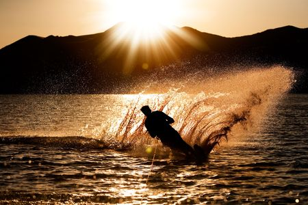 Ein männlicher Wasserski am Abend Sonnenuntergang